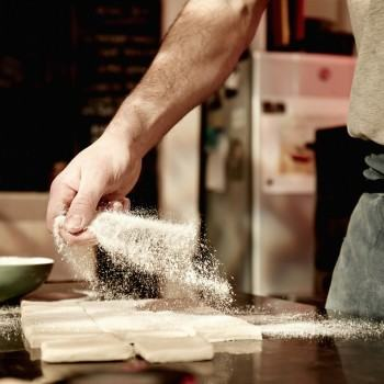 A baker working on a floured surface, dividing prepared dough into squares.